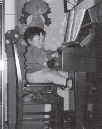 自宅のピアノの前で(1歳ころ)