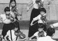 中西忠先生の門下生の合奏でヴァイオリンを<br /> 弾く(2列目右/7歳ころ)